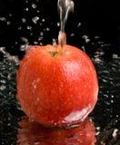 苹果红色飞溅流在水之下 免版税库存图片