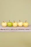 苹果行在土气木长凳的 免版税库存照片