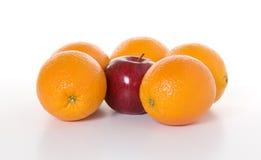 苹果被吊边的桔子 库存照片