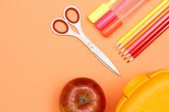 苹果计算机、剪刀、毛毡笔、颜色铅笔和午餐盒 学校 库存照片