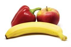 苹果计算机、胡椒和香蕉在白色背景 免版税库存照片