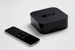 苹果计算机与遥控的电视第4一代 库存图片