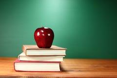 苹果计算机加上堆在一张书桌上的书回到学校的 免版税库存图片