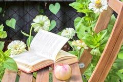 苹果计算机和书在一把木椅子在花中 库存图片