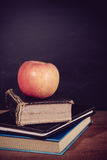 苹果计算机和书有黑板背景 免版税库存照片
