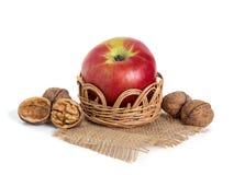 苹果计算机和坚果在篮子 免版税库存照片
