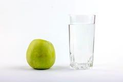 苹果计算机和杯水 免版税库存图片