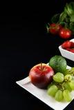 苹果计算机和果子在黑暗的backround 免版税库存照片
