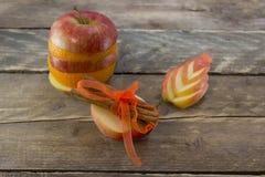 苹果计算机和桔子用桂香棍子在一张木书桌上 免版税库存图片