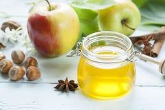 苹果计算机和蜂蜜在轻的木桌上 免版税库存图片