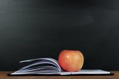 苹果计算机和被打开的书有黑板背景 免版税库存图片