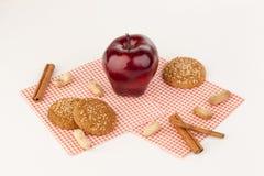 苹果计算机和麦甜饼在一张白色桌上 库存图片