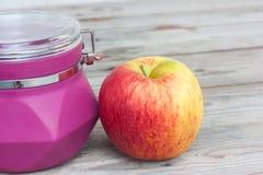 苹果计算机和紫色瓶子 库存照片