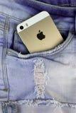 苹果计算机在一个蓝色牛仔布口袋的金子iPhone 5s 库存照片