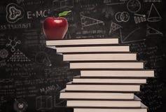 苹果计算机教育标志和堆在类的书 免版税图库摄影