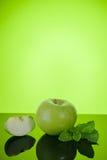 苹果计算机用在绿色的薄菏 免版税库存图片