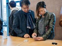 苹果计算机的亚裔种族夫妇顾客存放iPhone x 图库摄影