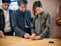 苹果计算机的亚裔种族夫妇顾客存放iPhone x 库存图片