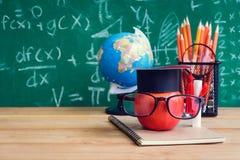 苹果计算机知识标志和铅笔书在书桌上有板的b 图库摄影