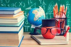 苹果计算机知识标志和铅笔书在书桌上有板的b 免版税库存照片