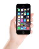 苹果计算机空间灰色iPhone 5S在女性手, desi上的显示iOS 8 免版税库存图片