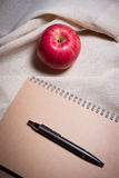 苹果计算机笔和笔记本在白色奶油色颜色织品 免版税库存图片