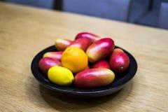 苹果计算机芒果、桔子和柠檬在碗在厨房里 图库摄影