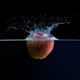 苹果计算机落入水 浇灌飞溅 免版税库存图片