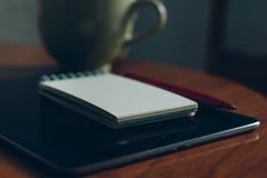 苹果计算机iPad、在木书桌上的咖啡和笔记本 库存图片