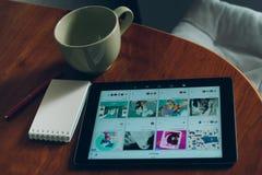 苹果计算机iPad、在木书桌上的咖啡和笔记本 免版税库存图片