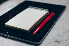 苹果计算机iPad、笔和笔记本在格子花呢披肩 免版税库存照片