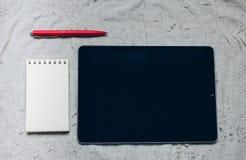 苹果计算机iPad、笔和笔记本在格子花呢披肩 免版税库存图片