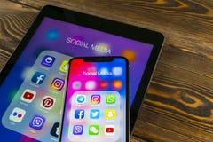 苹果计算机iPad和iPhone x与社会媒介facebook, instagram,慌张,在屏幕上的snapchat应用象  社会媒介象