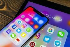 苹果计算机iPad和iPhone x与社会媒介facebook, instagram,慌张,在屏幕上的snapchat应用象  社会媒介象 免版税库存照片