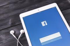 苹果计算机iPad赞成与在显示器屏幕上的Facebook主页 最大的社会网络网站的Facebook一 facebook.com主页 免版税库存图片