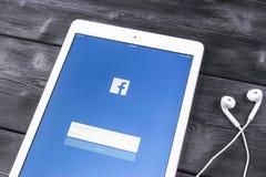 苹果计算机iPad赞成与在显示器屏幕上的Facebook主页 最大的社会网络网站的Facebook一 facebook.com主页 免版税库存照片