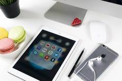 苹果计算机iPad赞成在与社会媒介facebook, instagram,慌张,在屏幕上的snapchat应用象的办公室桌上  片剂 库存图片