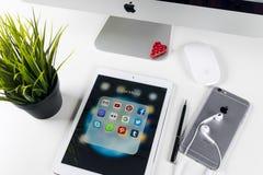 苹果计算机iPad赞成在与社会媒介facebook, instagram,慌张,在屏幕上的snapchat应用象的办公室桌上  片剂 库存照片