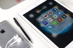 苹果计算机iPad赞成在与社会媒介facebook, instagram,慌张,在屏幕上的snapchat应用象的办公室桌上  片剂 图库摄影