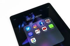 苹果计算机iPad赞成在与社会媒介facebook instagram慌张应用象的白色桌上在屏幕上的 片剂计算机生活st 免版税库存图片