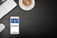 苹果计算机iPhone与Facebook app的8个加号在屏幕上 免版税库存照片