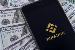 苹果计算机iPhone和Binance商标和美元 Binance是cryptoc 免版税图库摄影
