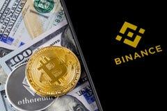 苹果计算机iPhone和Binance商标和bitcoin、ethereum和美元 免版税库存图片