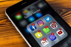 苹果计算机iPhone在木桌上的7个加号与社会媒介facebook, instagram,慌张,在屏幕上的snapchat应用象  聪明 库存图片