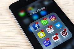 苹果计算机iPhone在白色木桌上的7个加号与社会媒介facebook, instagram,慌张,在屏幕上的snapchat应用象  免版税库存图片