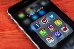 苹果计算机iPhone在红色木桌上的7个加号与社会媒介facebook, instagram,慌张,在屏幕上的snapchat应用象  S 免版税图库摄影