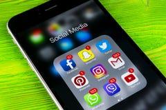 苹果计算机iPhone在绿色木桌上的7个加号与社会媒介facebook, instagram,慌张,在屏幕上的snapchat应用象  库存照片
