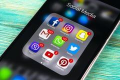 苹果计算机iPhone在蓝色木桌上的7个加号与社会媒介facebook, instagram,慌张,在屏幕上的snapchat应用象  免版税库存照片
