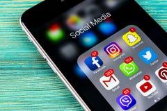 苹果计算机iPhone在蓝色木桌上的7个加号与社会媒介facebook, instagram,慌张,在屏幕上的snapchat应用象  图库摄影