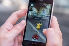 苹果计算机iPhone5s和从Pokemon的皮卡丘去应用,少年使用的手 免版税库存图片